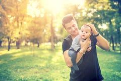 年轻男性,父亲举行3个月婴儿和有好时光在公园 父亲和儿子概念本质上 免版税库存照片