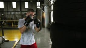 男性,白种人拳击手实践起动黑gloces使用由汽车轮胎做的一个puching的袋子 老牌拳击演播室 股票录像