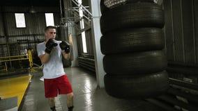 男性,解决与沙袋的积极的拳击手做由汽车轮胎 解决在拳击的黑拳击手套 股票录像