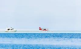 男性,马尔代夫- 2016年11月, 27日:水上飞机Trans Maldivian空中航线在水登陆了 空白游艇在海运 复制空间为 免版税图库摄影