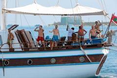 男性,马尔代夫2013年2月09日:没有风帆的老经典木小船在开阔水域 在美丽的帆船的看法以愉快 免版税库存图片