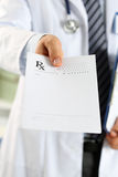 男性医学医生手举行剪贴板垫和给prescripti 库存图片