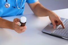 男性医学医生手拿着瓶子药片并且键入某事在便携式计算机键盘 万能药生活救球 免版税图库摄影