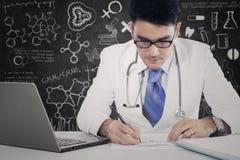 男性医师做医学食谱 免版税库存图片