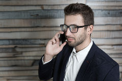 男性经济学家谈话在手机,当站立在moder时 免版税库存照片