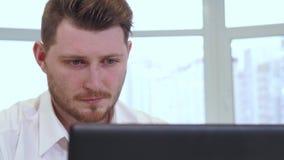 男性经理在办公室使用膝上型计算机