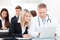 男性医生和女实业家有膝上型计算机的 免版税库存图片