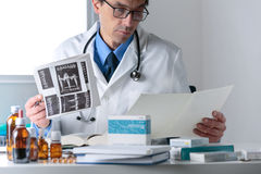 男性医生工作在他的办公室桌面的,审查的医疗Rep 图库摄影