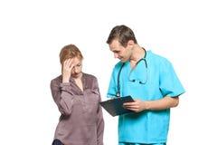 男性医生询问一名哀伤的妇女患者 免版税库存图片