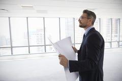 男性建筑师在看计划的现代空的办公室 免版税库存照片