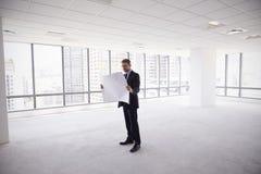 男性建筑师在看计划的现代空的办公室 图库摄影
