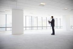 男性建筑师在看计划的现代空的办公室 免版税库存图片