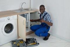 男性水管工定象水槽在厨房里 库存图片