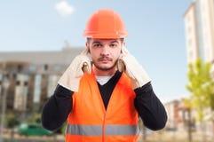 男性建设者做听不到邪恶的姿态 库存照片