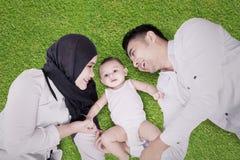 男性说谎在草的婴孩和父母 图库摄影