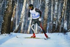 男性滑雪者在桦树森林里赛跑经典样式在冬天 库存图片