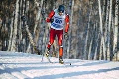 年轻男性滑雪者经典样式在滑雪区域的冬天森林里 库存图片