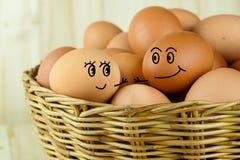 男性去鸡蛋和女性的鸡蛋握他们的在一个柳条筐的手在木背景中 免版税库存图片