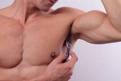 男性depilacion 使用剃刀的年轻可爱的肌肉人从他的腋窝取消头发 免版税库存图片
