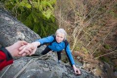 男性rockclimber帮助一位登山人女性 库存照片