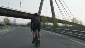 男性triathlete乘坐的自行车作为他的训练进度表的部分 他戴黑成套装备、盔甲和太阳镜 r 股票视频