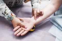 男按摩师做手按摩给一名妇女在医疗办公室 库存图片