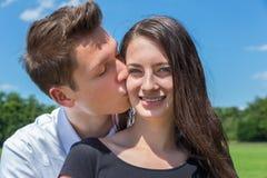 男朋友亲吻面颊的女朋友在晴朗的自然 库存照片