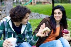 男朋友吸引的女朋友用反对她的健康苹果的汉堡包 库存照片