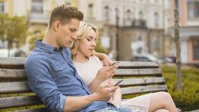 男朋友和女朋友坐长凳,大字书写在电话,网络 库存照片