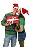 男朋友女孩亲吻当前圣诞老人的帽子&# 免版税库存图片