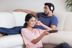 男朋友她的电视注意的妇女 免版税库存图片