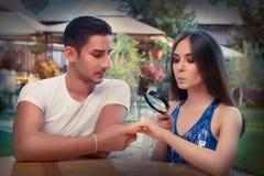 从男朋友的好奇女孩测试定婚戒指有放大器的 图库摄影