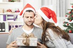 男朋友看起来怀疑对他的圣诞节礼物 库存图片
