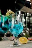 男服务员倾吐从振动器的一个蓝色盐水湖鸡尾酒入玻璃在酒吧 鸡尾酒准备 免版税库存图片
