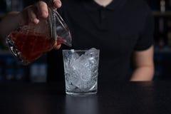 男服务员倾吐从量杯的酒精入在冰的一块玻璃 库存图片