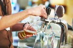 男服务员倾吐的啤酒 免版税库存图片