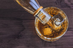 男服务员倾吐的威士忌酒看法上面在玻璃的与在木桌背景,在冰块的焦点的冰块 免版税库存图片