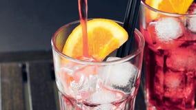男服务员倾吐的红色喷开胃酒与两个橙色切片和冰块的aperol鸡尾酒在木头 股票录像