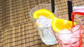 男服务员倾吐的红色喷开胃酒与两个橙色切片和冰块的aperol鸡尾酒 股票录像