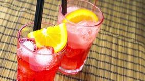 男服务员倾吐的红色喷开胃酒与两个橙色切片和冰块的aperol鸡尾酒 影视素材