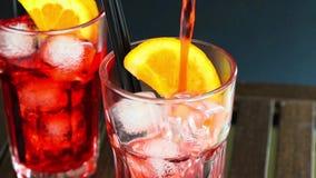 男服务员倾吐的红色喷开胃酒与两个橙色切片和冰块的aperol鸡尾酒 股票视频