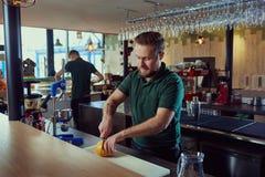 男服务员准备新鲜的汁液在酒吧 库存图片
