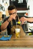 男服务员在准备杜松子酒补剂鸡尾酒的客栈或餐馆 免版税库存图片