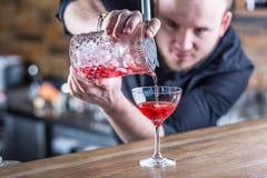 男服务员在准备鸡尾酒饮料的客栈或餐馆 图库摄影