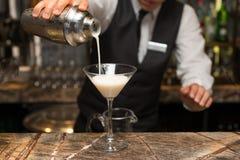 男服务员在工作,准备鸡尾酒 对鸡尾酒杯的倾吐的pina colada 免版税库存图片
