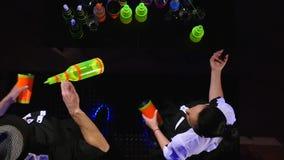 男服务员展示 两个男服务员玩杂耍瓶和烧杯混合的 慢的行动 顶视图 股票录像