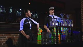 男服务员展示 两个男服务员玩杂耍瓶和烧杯混合的 慢的行动 股票视频