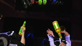 男服务员展示 两个男服务员玩杂耍瓶和烧杯混合的 顶视图 影视素材