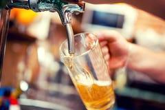 男服务员手特写镜头在倒桶装啤酒的啤酒轻拍的 免版税库存图片