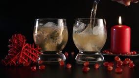 男服务员` s手倾吐的姜汁无酒精饮料用苏格兰威士忌利口酒到玻璃里有很多冰,特写镜头 在黑色隔绝的静物画 股票视频